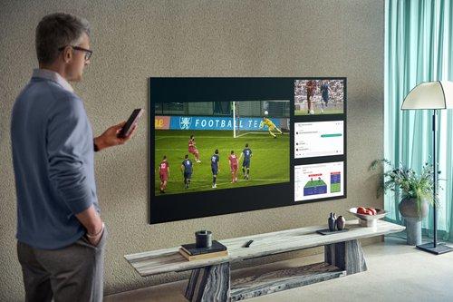 Mężczyzna stojący w salonie przy telewizorze Samsung Neo QLED QN91A MiniLED
