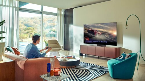 Telewizor LCD Mini LED i grający mężczyzna siedzący na kanapie